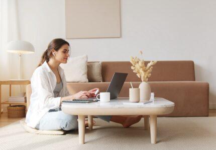 Kvinde sidder på gulv og arbejder på computer
