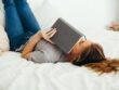 Kvinde læser bog i sin seng
