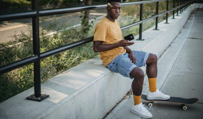 Ung mand sidder med sit skateboard